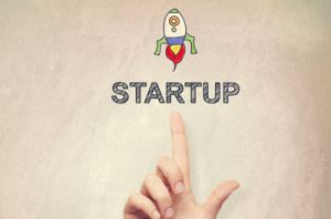 Hand pointing to Startup concept on light brown wall background